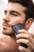 picture of shaved head  - Handsome young man is shaving with electric razor while looking at the mirror - JPG