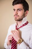 foto of tied  - Confident young man in white shirt is tying his necktie and looking away - JPG