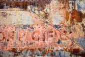 picture of railroad car  - A side panel of an old railroad car is covered with rust peeling paint and old rivets in a post - JPG