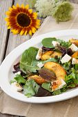 picture of vinegar  - Plate of grilled peach and Mozzarella salad with mixed baby greens and balsamic vinegar in a rustic setting - JPG