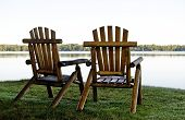 picture of shoreline  - duo of log chairs on the shoreline of a peaceful lake - JPG