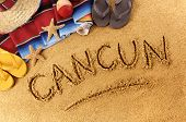 stock photo of maracas  - The word Cancun written in sand on a Mexican beach with sombrero straw hat traditional serape blanket starfish and maracas - JPG