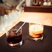 stock photo of marsala  - Black russian and white russian cocktails on the bar stand on rubber mat. Shallow DOF and marsala tonned ** Note: Visible grain at 100%, best at smaller sizes - JPG