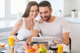 picture of bonding  - Beautiful young couple bonding to each other and reading newspaper together while sitting in the kitchen and having breakfast - JPG