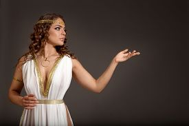 stock photo of toga  - The Beautiful Young Woman Wearing White and Gold Greek Costume Looking to Something on her Left on the Dark Background - JPG