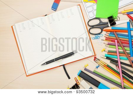 School and office supplies over office table. Top view with notepad for copy space