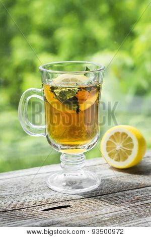 Green Tea With Mint And Lemon In A Glass Mug On A Light Wooden Background