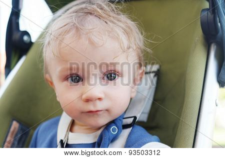Close up Portrait of a Cute White Blond Baby Boy on his Stroller, Looking Into the Distance.