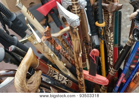 Box of assorted decorative walking sticks or canes with ornamental handles in different shapes, some hand carved wood, displayed in store for purchase