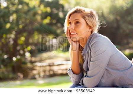 thoughtful young woman sitting outdoors