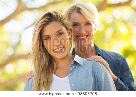 happy mid age mother behind her daughter outdoors