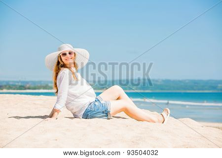 Beautifil young woman lying on the beach at sunny day enjoing summer vacation