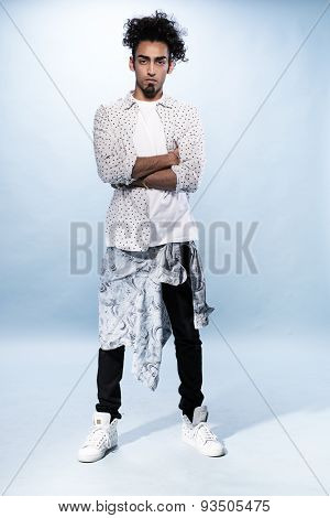 Full Length Shot of a Stylish Young Hip Hop Male Dancer with Curly Hair, Staring at the Camera with Arms Closed Over his Stomach, Captured in Studio with White Background.