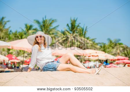 Beautifil young woman sitting on the beach at sunny day enjoing summer vacation