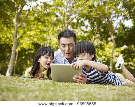 Asian Father And Children Using Tablet Computer Outdoors