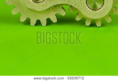 Metal shiny cogwheel element shot on green paper background as closeup image