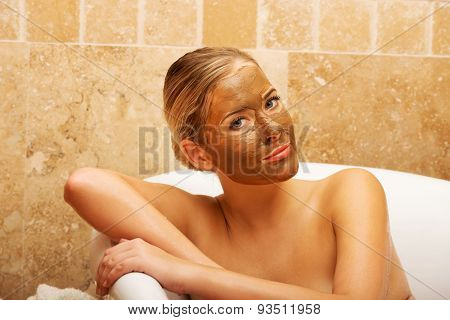 Relaxed spa woman sitting in a bath with face mask
