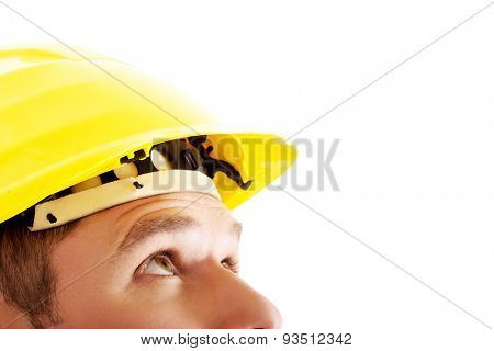 Portrait of a man with hardhat looking up.
