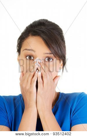 Frightened woman covering with hands her mouth.