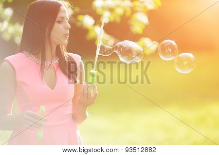 Young spring fashion woman blow bubbles Trendy girl in flowering trees in spring summer garden Springtime or summertime Lady in spring landscape background Allergic to pollen of flowers Spring allergy