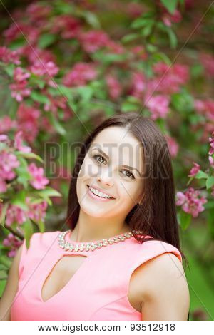 Young spring fashion woman. Trendy girl in the flowering trees in the spring summer garden. Springtime or summertime. Lady in spring landscape background. Allergic to pollen of flowers Spring allergy