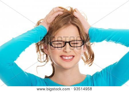 Young angry teenager pulling her hair