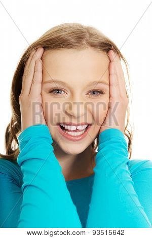 Excited teenage woman holding her head