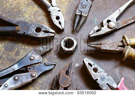 Group Of Vintage Pliers Teamwork Turning Nut