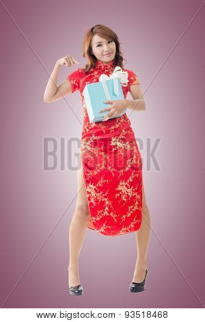Smiling Chinese woman dress traditional cheongsam standing and holding a gift box at New Year, full length portrait isolated.