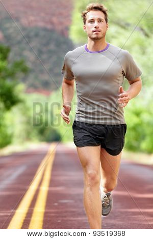 Man running on road. Sport and fitness runner training for marathon run doing workout outdoors in summer. Male athlete sports model fit and healthy aspirations.