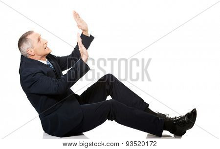 Frightened businessman protecting himself from empty space.