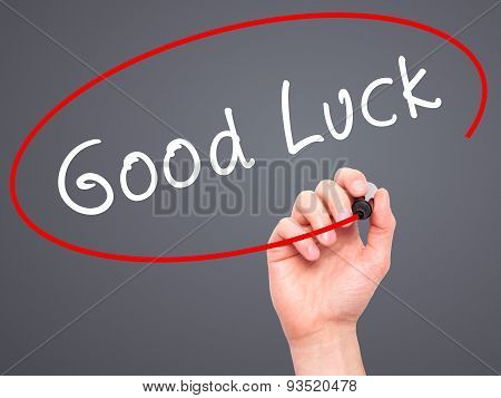 Man Hand writing Good Luck with marker on transparent wipe board.