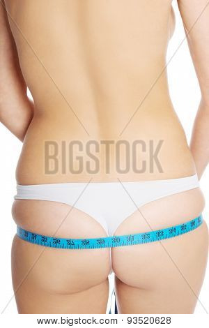 Back view of a woman measuring her buttocks.