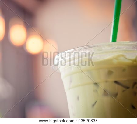 Plastic Cup Of Iced Matcha  With Green Straw In Creamy Tone Like Instagram Filter