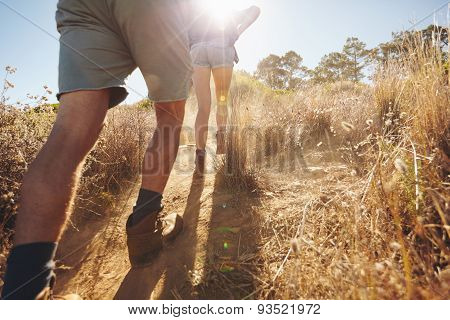 Two People Going Uphill On A Mountain Trail