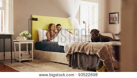 Young Couple Sharing A Digital Tablet While Relaxing In Bed