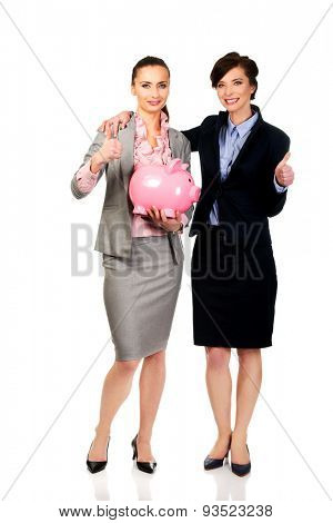 Two businesswoman with thumbs up holding a piggybank.