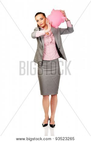 Caucasian businesswoman shaking a piggybank.