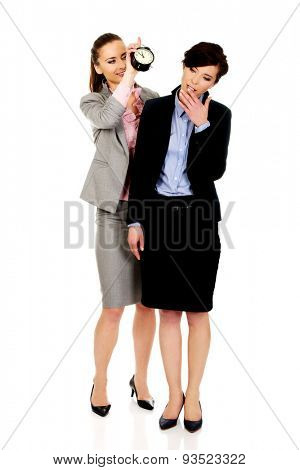 Businesswoman waking up her partner with alarm clock.