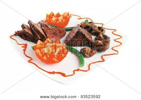 roast fillet mignon on a white ceramic plate with tomatoes