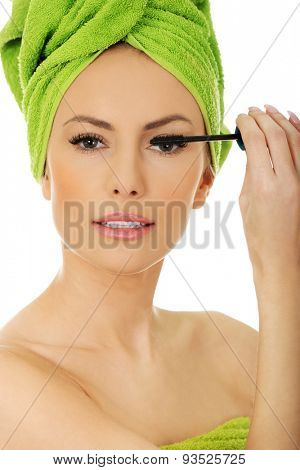 Woman with towel turban applying mascara.