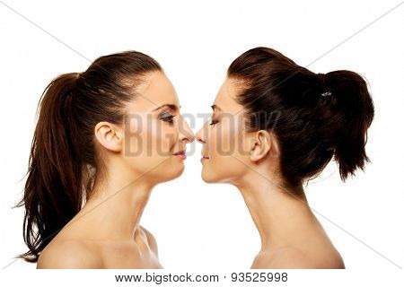 Two attractive sisters standing face to face.
