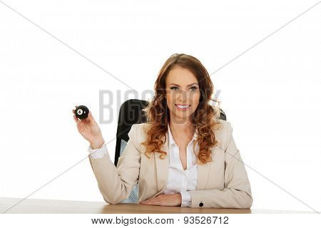 Businesswoman holding eight billiard ball by a desk.