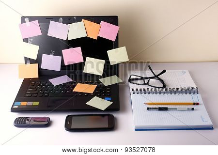 Laptop computer with colorful papers, cellphone, smartphone, notebook, pen, pencil and eyeglasses
