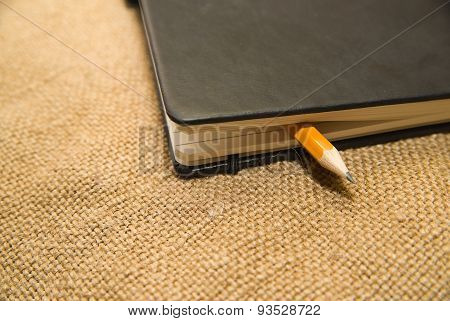 Notebook And Pencil On The Old Tissue