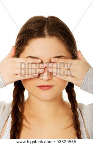 Teen woman covering her eyes with both hands.