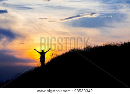 Silhouette of woman with raised hands