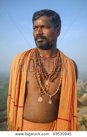 KAMALAPURAM, INDIA - 03 FEBRUARY: Indian pilgrim with religious necklaces and scarf on hilltop