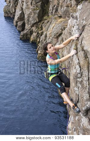 Female extreme climber conquers steep rock