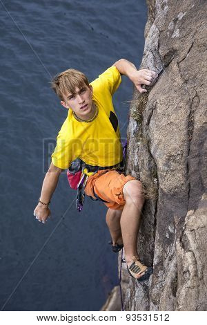 Young male rock climber hanging over the water